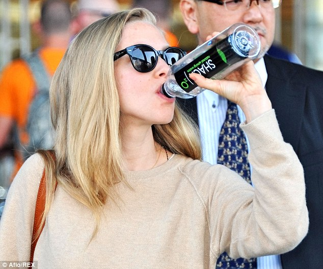 Rehydrating after the flight: The Les Miserables star slugged back a litre of bottled water after the long flight