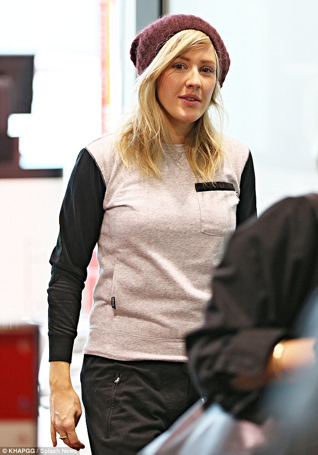 Dressing for the weather: She tucked her beautiful blonde locks into a woolie maroon beanie, and kept warm with the help of a black-sleeved grey sweater