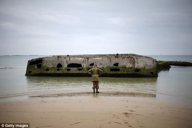 A young boy, who is  part of a WWII reenactment group, walks along 'Gold Beach' and looks at part of a Mulberry pontoon at Arromanche