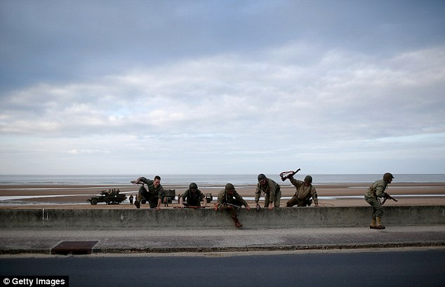 A group of World War II re-enactors from Spain practice scaling a seawall on the Avenue de la Liberation that runs parallel to Omaha Beach June in Vierville, France