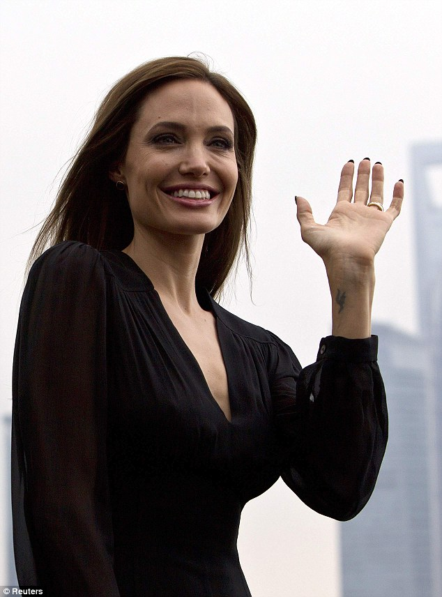 Actress Angelina Jolie waves during a photocall as she takes part in a promotional tour for the film Maleficent in Shanghai