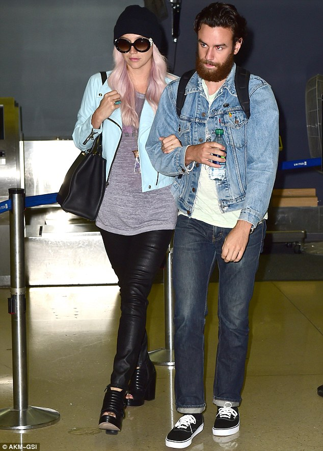 Airport chic: The singer sported oversized rounded sunglasses, a blue cropped jacket and leather trousers