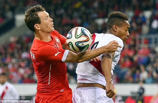 Battle: Switzerland's Stephan Lichtsteiner keeps Peru's Andre Carrillo at bay