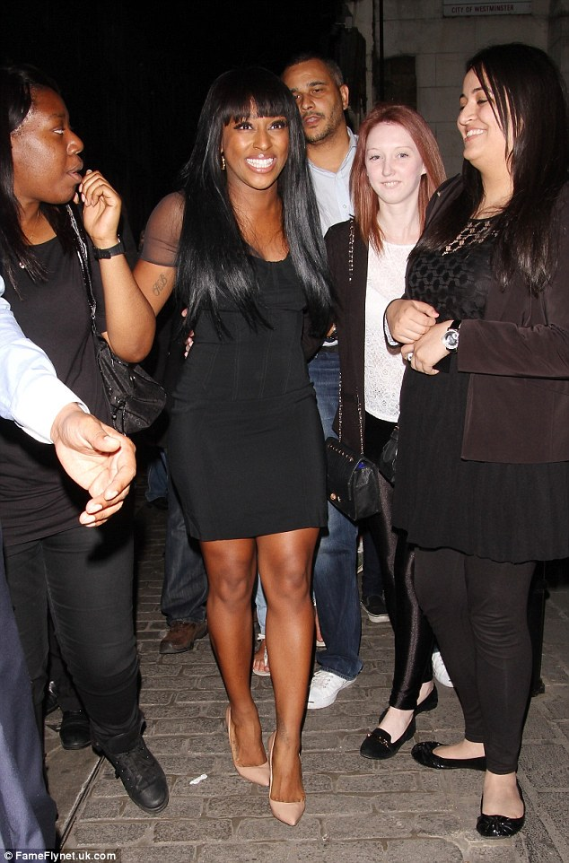 Celebration time: The singer was flanked by a group of girls as she left the Strand theatre