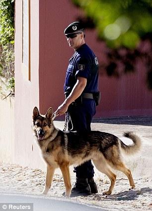A dog and its Portuguese police handler are seen in Praia da Luz