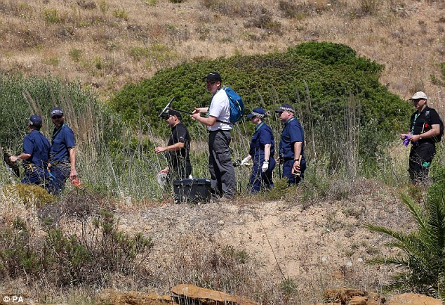 Methodical: British police check another specific  area of the scrubland with the man in the centre digging for samples