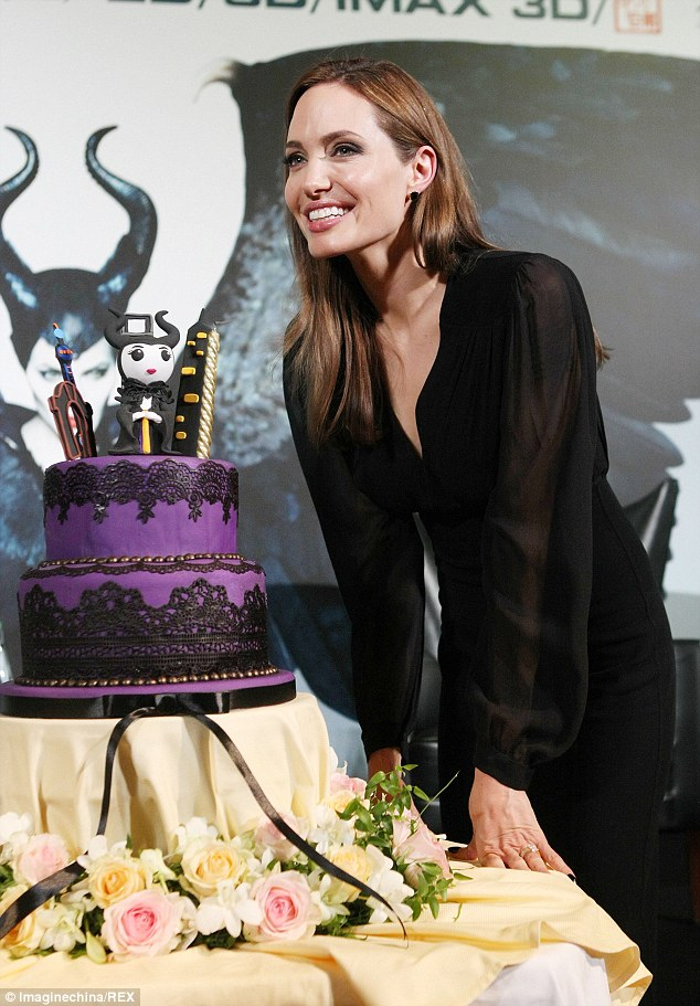 Having her cake and eating it! Angelina Jolie celebrates the Maleficent press conference in  Shanghai, China