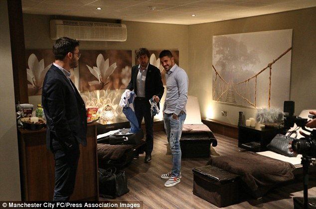 History boy: David Villa and his agent in the lounge before his medical