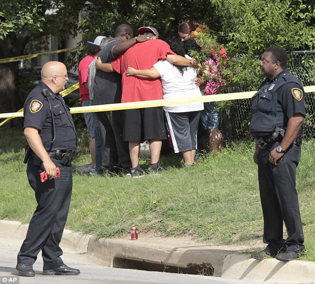 Support: Family and friends gather for a moment of reflection as police stand guard outside the house