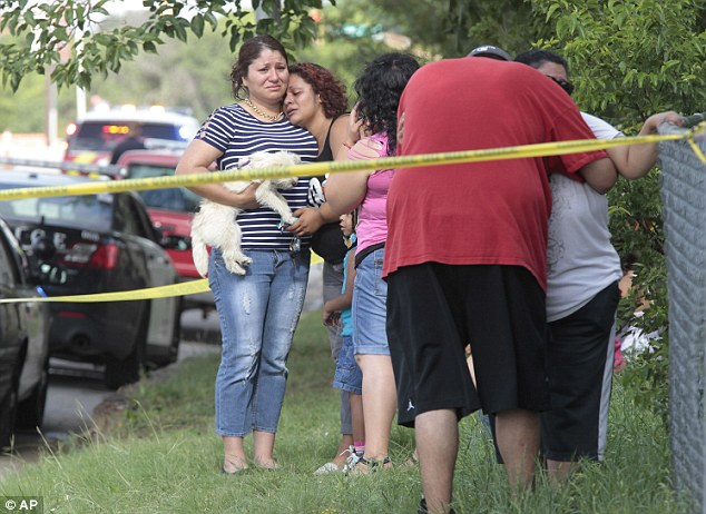 Shock: Grieving family and friends gather outside the Fort Worth home where three women were killed
