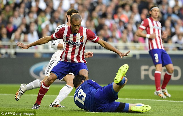 Safe: Courtois smothers the ball during the Champions League final, which Atletico lost 4-1 to neighbours Real