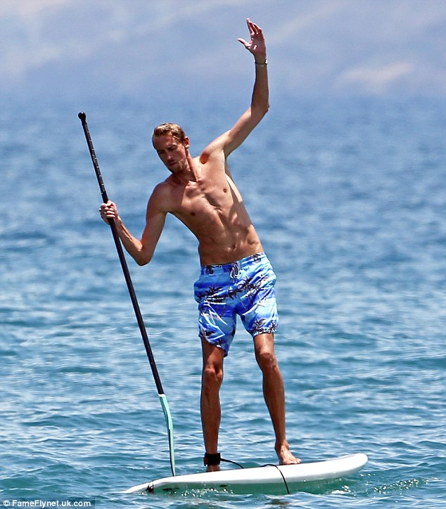 Hawaii five-whoa: Peter Crouch suddenly loses his balance as he stands on a paddle-board in Hawaii on Tuesday