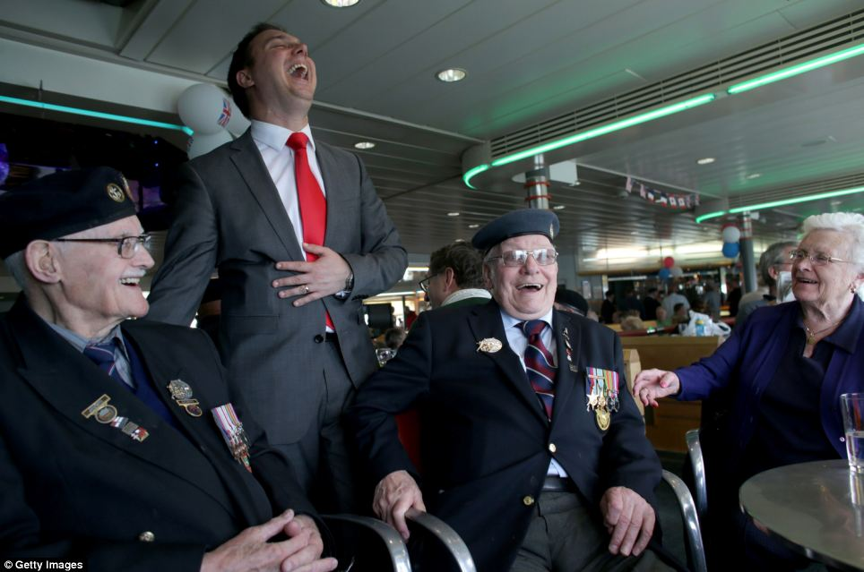 The ship's entertainments manager Adam Bowles jokes with veterans Robert Browne, 89 who was in the Royal Navy and Bert Turner, 90, who was in Bomber Command