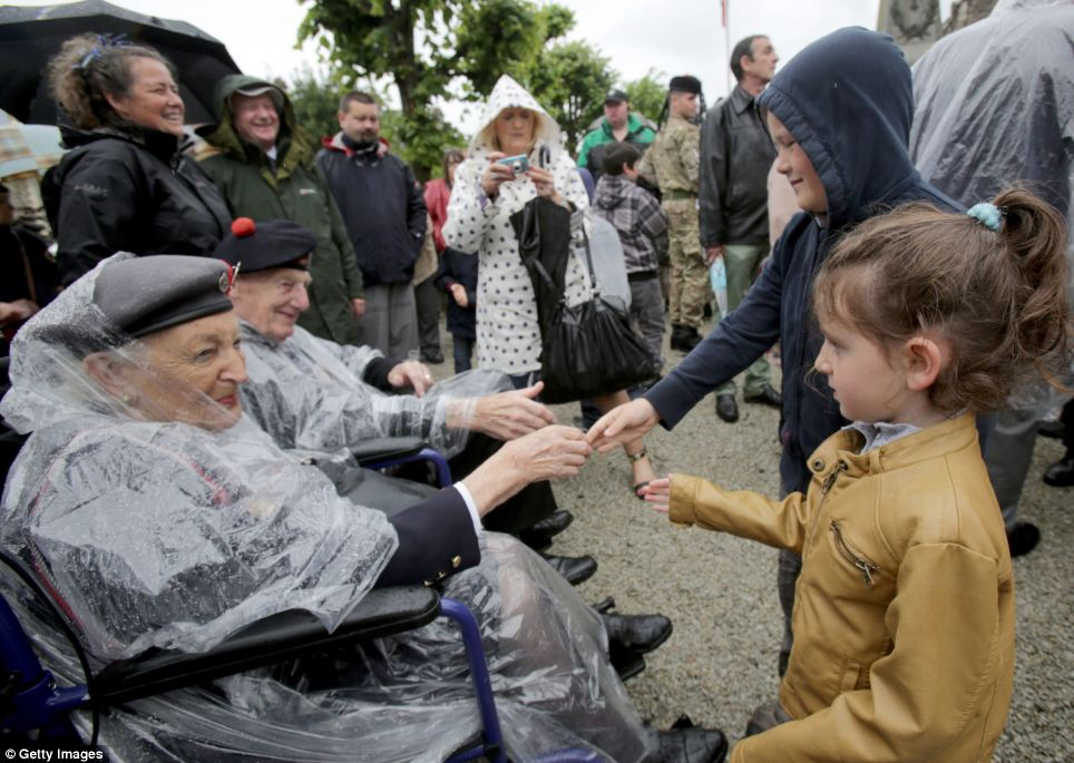 Vera Hay, 92, who was a nurse in a field hospital shortly after D-Day, is greeted by children in the small town of Thury-Harcourt after making the trip to France