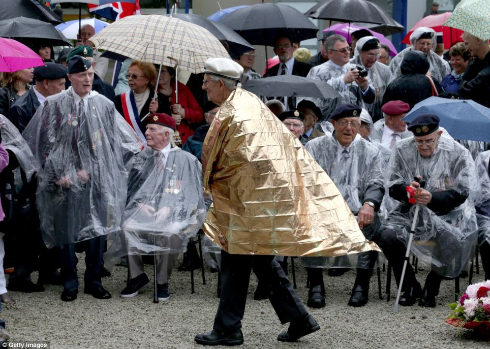 The veterans were undeterred by the wet Normandy weather and donned ponchos and blankets and sheltered under umbrellas for the service in the town near Caen