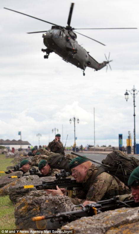 Men prepare to fire their weapons and a military aircraft soars above them, left, while on the right one marine takes a moment to take in the scene