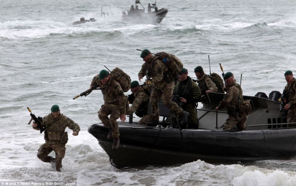 In dramatic photographs, the marines from squadron HMS Bulwark in Plymouth piled out of boats - running up towards the beach through the shallow waters in Portsmouth. Their amphibious assault demonstration will lead the memorial celebrations in the town today