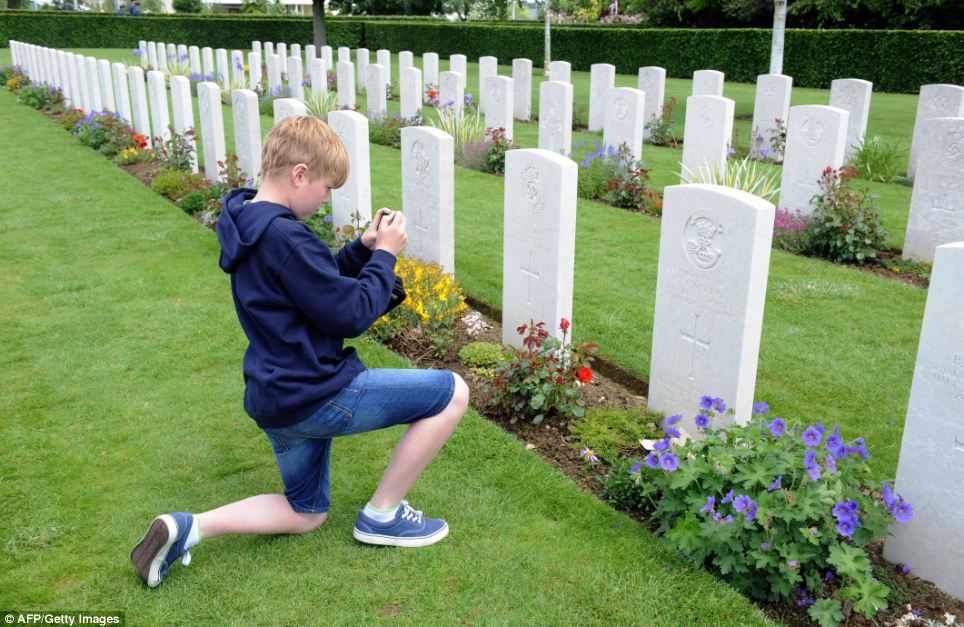 A young boy takes a photo of the grave of his great-uncle at the Bayeux War Cemetery in the city of Bayeux, northern France