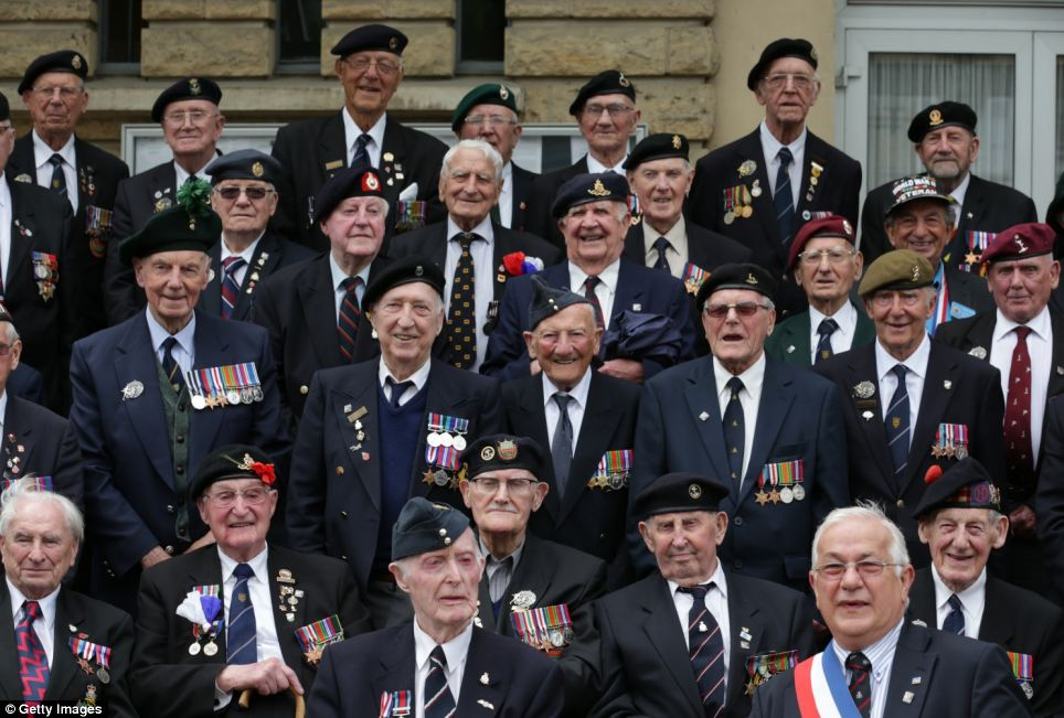 A group of veterans gather for a photograph with the local mayor at a civic function in the village of Thury-Harcourt near Caen during their action packed day