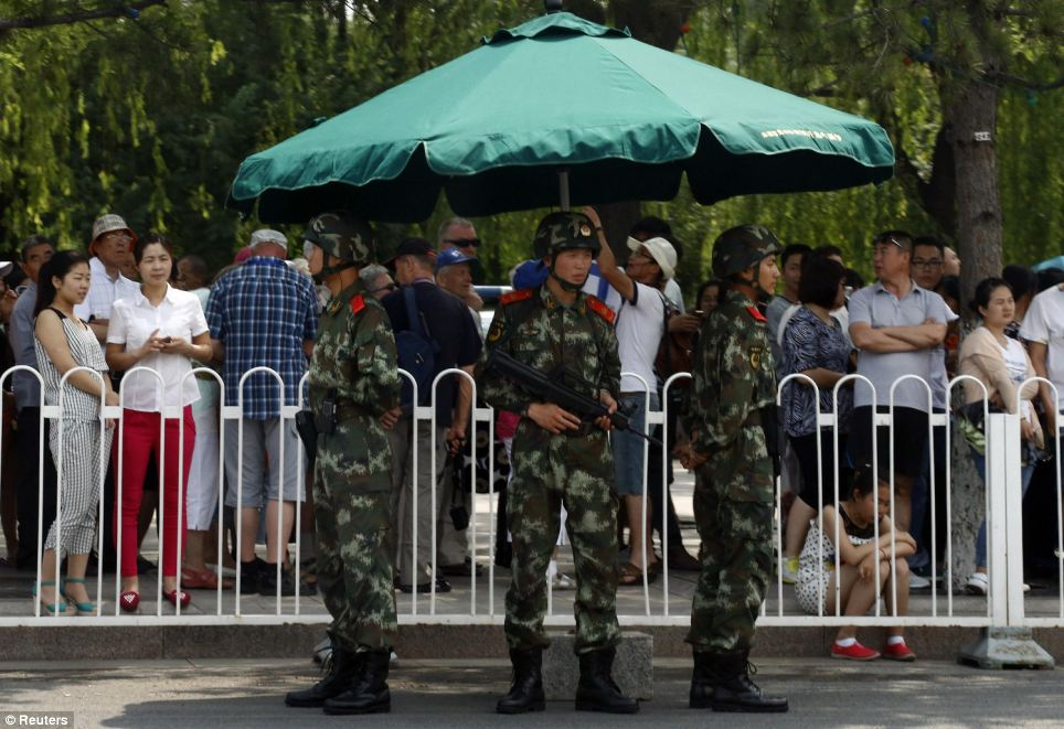 Paramilitary soldiers stand guard in front of visitors in a queue to undergo security checks before entering Tiananmen Square