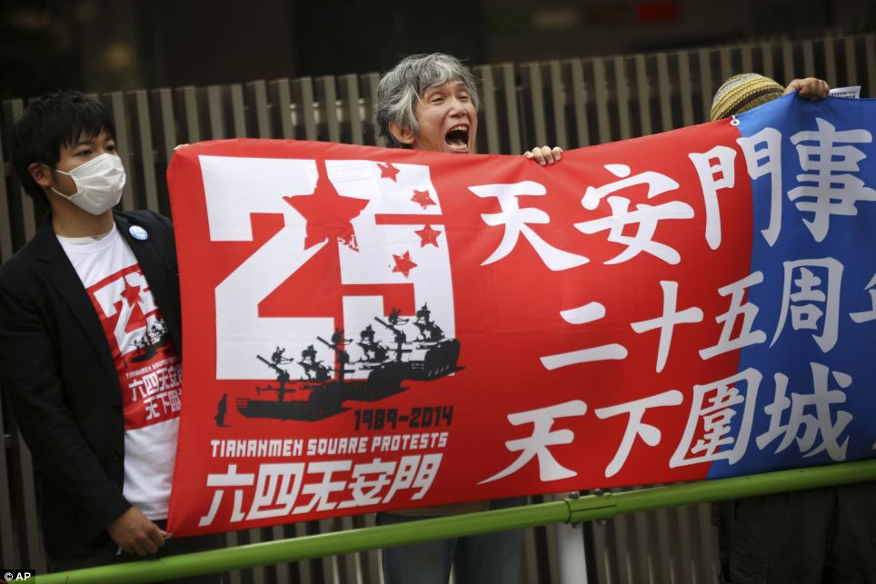 A protester holds a banner with others and shouts slogans in front of the Chinese Embassy in Tokyo