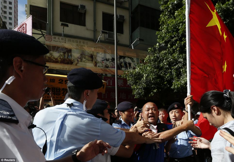 Police stop a pro-China protester carrying a Chinese flag as he attempts to approach anti-Chinese demonstrators during a rally near Hong Kong's Victoria Park