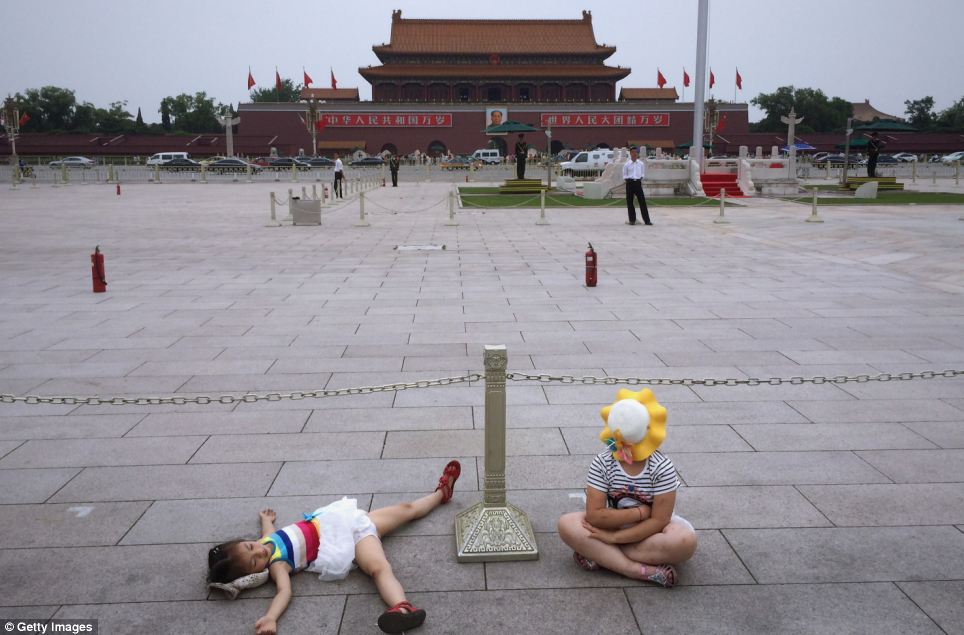 Two Chinese young people rest in a deserted Tiananmen Square - 25 years on from the infamous clashes in the area which led to the deaths of scores of protesters