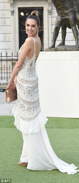 Classy: She teamed the cream gown which a shimmering metallic gold clutch and cream high heels while she styled her long locks into a simple top knot