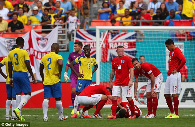 In pain: England players look glum as they surround the hurt Arsenal midfielder