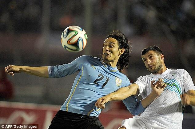 Big hitter: Cavani (left) vies for the ball with Slovenia's Jokic Bojan at the Centenario Stadium in Montevideo