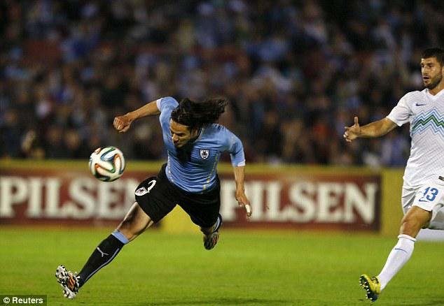 One up: Uruguay's Edinson Cavani heads in his side's opener in Montevideo