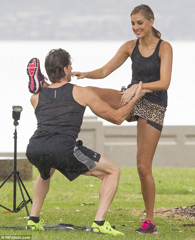 Legs a-kimbo! The 26-year-old struck a variety of poses as she worked alongside a trainer at the rainy beach location