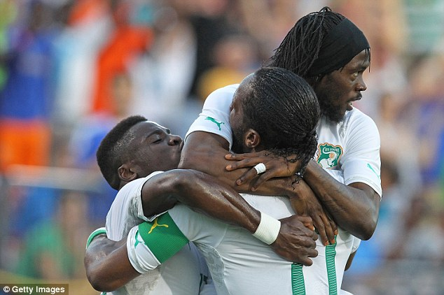 Teamwork: Gervinho and Drogba embrace during a fairly comfortable win for the Elephants, who line up alongside Greece, Colombia and Japan in their World Cup group