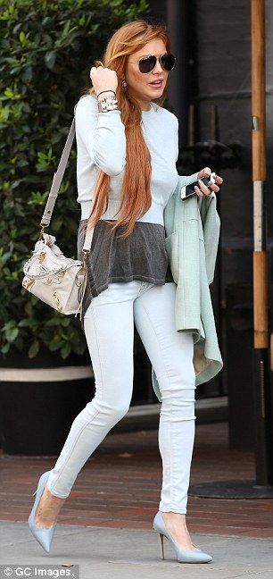 Best foot forward: The actress wore ice blue skinny jeans with a matching crop jumper atop a dark grey top while she held onto a baby blue coat