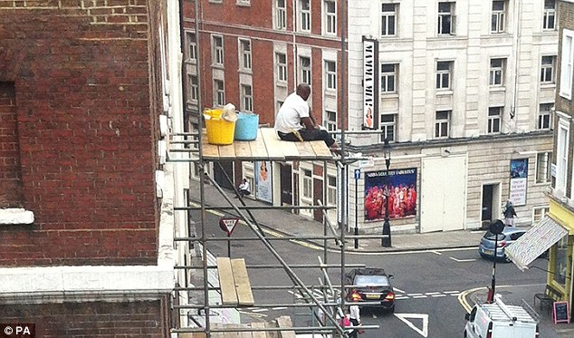 Dangling: Health and safety authorities were sent this picture of a worker precariously perched on top of a five-storey-high scaffolding