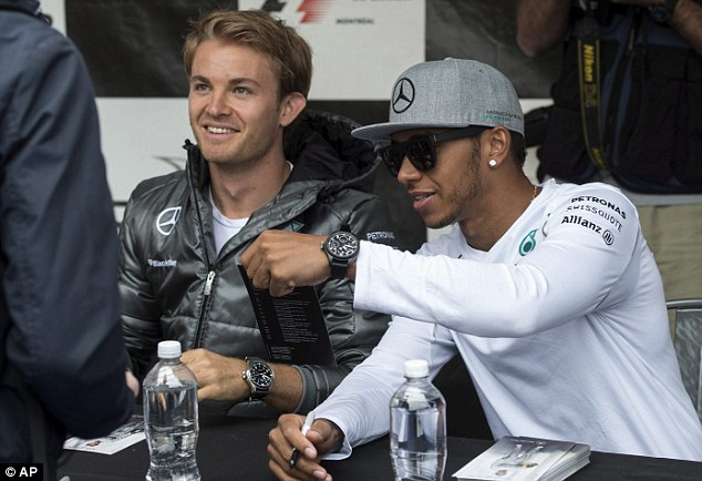 Pictured together: Nico Rosberg and team-mate Hamilton penned autographs at a signing session on Thursday