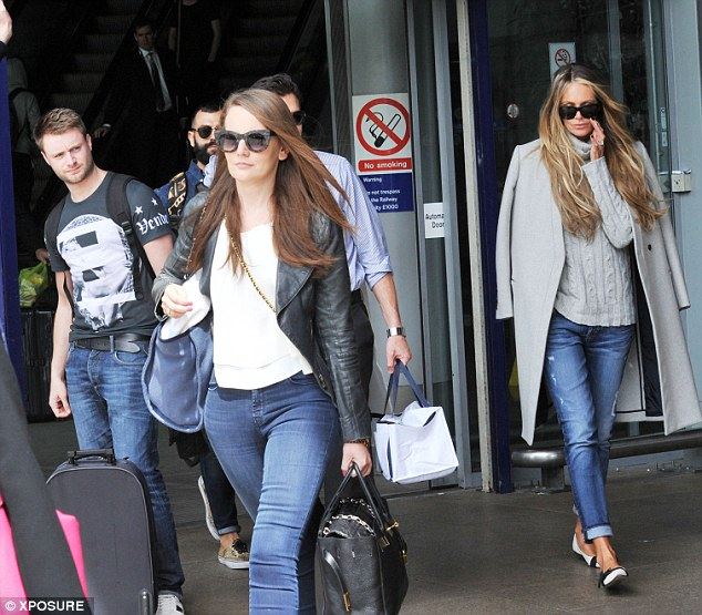 Stepping gout: The supermodel mingles with fellow travellers as she makes her way out onto the street on Friday