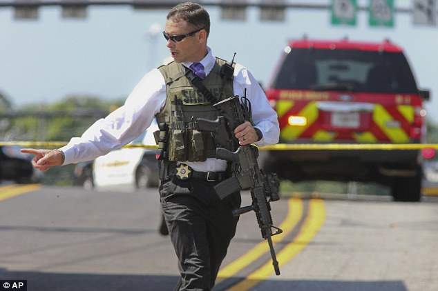 Response: Heavily armed members of the Sheriff's department clear the scene after Deputy Rush was shot in the leg