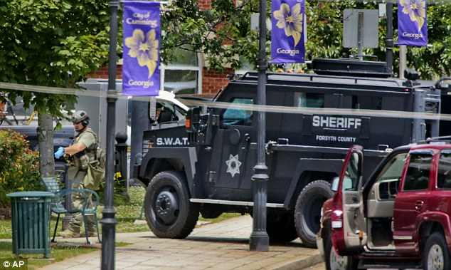 Search: Members of a SWAT team swarm over the courthouse after the confrontation with Marx on Friday