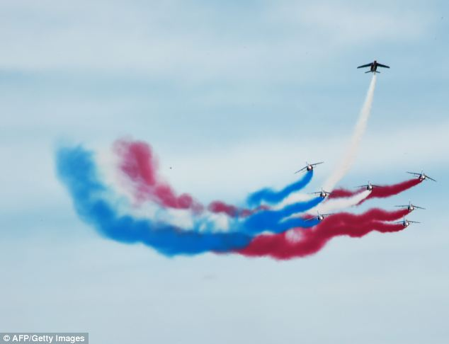 Show: Alpha jets, part of the Patrouille Acrobatique de France, leave trails of smoke in the colors of the French flag during the ceremony
