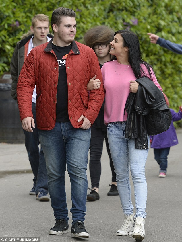 Growing lad: Kym's son towers over his mother as they walk around the theme park