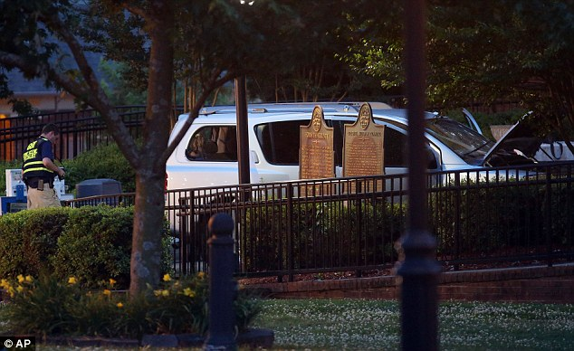Aftermath: A Georgia Bureau of Investigation worker passes by the rented SUV used by accused Forsyth County Courthouse shooter Dennis Marx