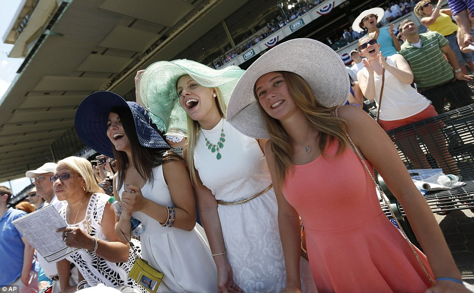 On track: Friends cheer on the horses in an early race as they wait for California Chrome to make his challenge for the main event this evening