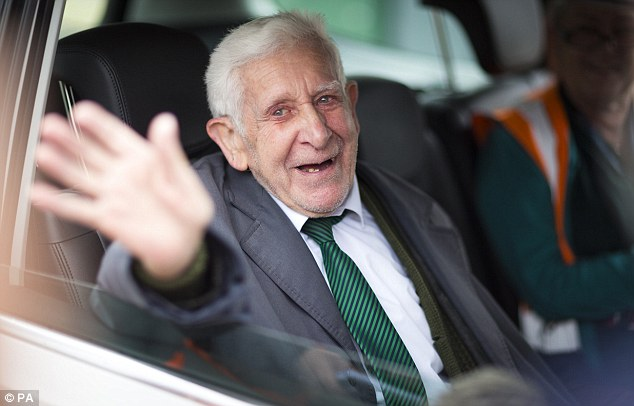 Grin: He waved to photographers as he was driven away from the ferry port