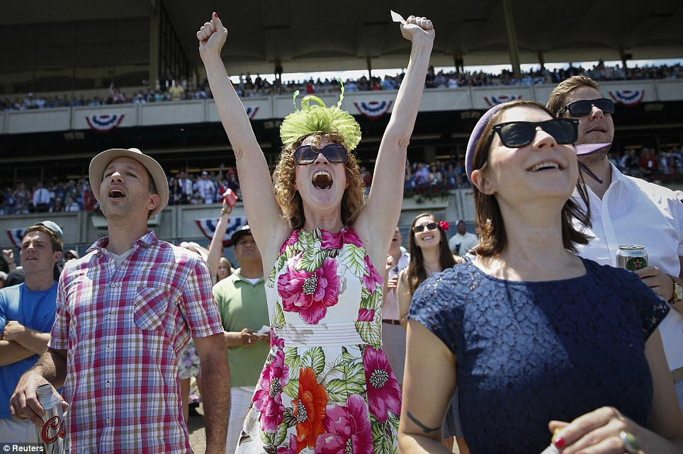 Sweet victory: Shayna Reade (C) cheers as horses cross the finish line during the third race at Belmont Park before the 2014 Belmont Stakes