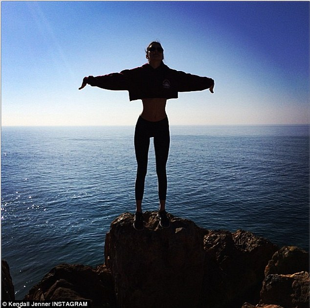 It's a tough life! While Kim and Kanye were celebrating, Kendall Jenner shared a picture of herself wearing leggings and a cropped sweater as she posed on a rock in front of the ocean
