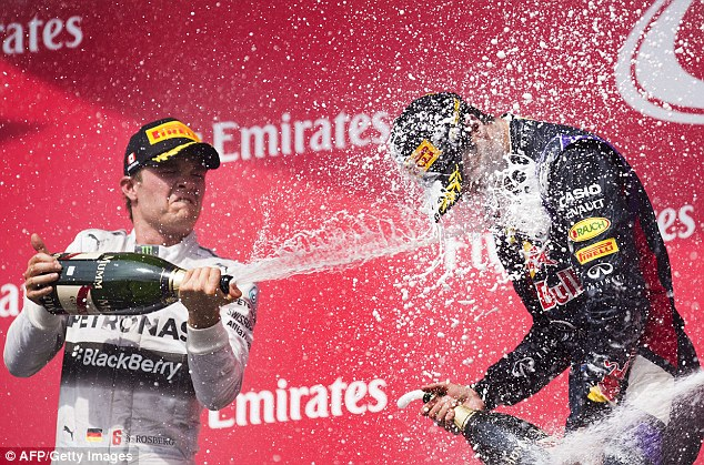 Shower time: Second-placed Rosberg sprays champagne over the winner Ricciardo