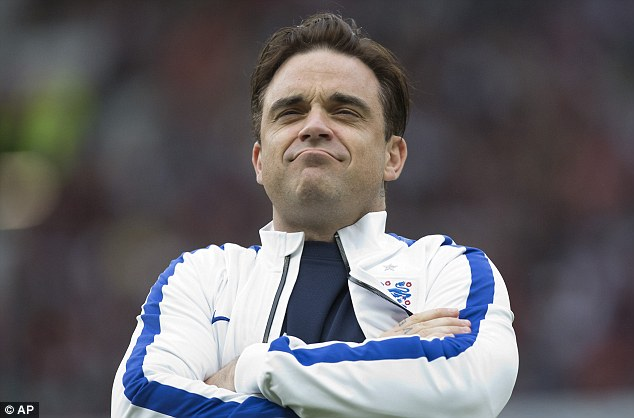 Looking confident: Popstar Robbie Williams was forced to miss the game after injuring his back
