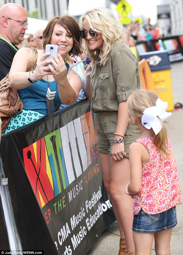 Looking up to mom: Maddie, who turns six on June 19, wore a cute summery ensemble as she watched Jamie snap mementos with fans