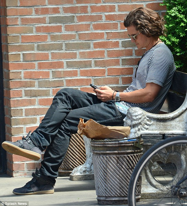Rest time: Orlando was later seen perched on a park bench perusing his mobile device
